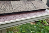 Brown gutter covers on white gutters