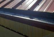 Black gutter guards installed with a metal roof